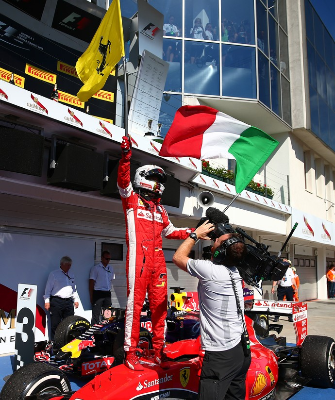 Sebastian Vettel com as bandeiras da Ferrari e da Itália após vitória no GP da Hungria de Fórmula 1 2015 (Foto: Getty Images)