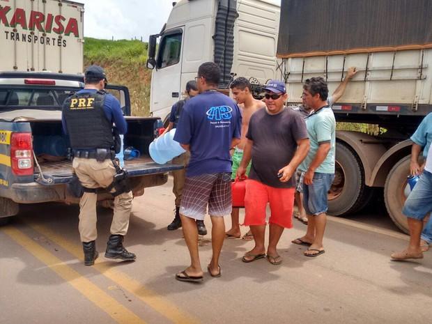 PRF distribui água aos caminhoneiros e familiares, retidos no longo congestionamento (Foto: Ascom/PRF)