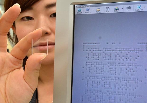 A fabricante japonesa Hitachi apresentou uma placa feita de quartzo com uma nova tecnologia que pode armazenar uma quantidade quase infinita de dados. Um laser grava pequenos pontos na placa de quartzo que são reconhecidos pelo computador como dados binár (Foto: Yoshikazu Tsuno/AFP)