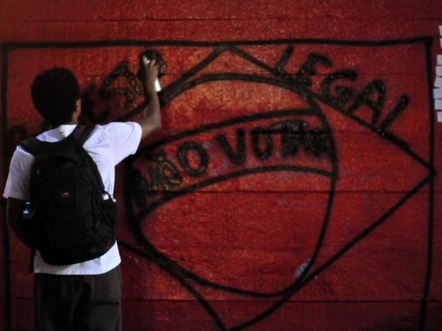 Jovem picha o desenho de uma bandeira do Brasil com uma mensagem de protesto em um dos pilares do Masp, na Avenida Pauulista, na região central de São Paulo, durante protesto contra a Copa do Mundo 2014 no Brasil (Foto: Cris Faga/Fox Press Photo/Estadão Conteúdo)