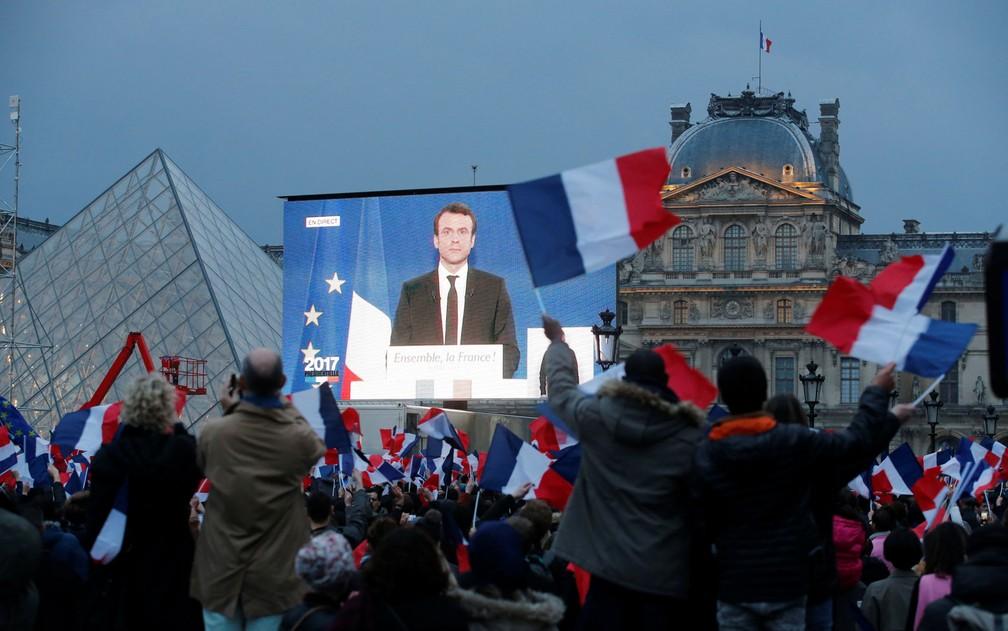 Macron é visto em telão montado próximo ao Museu do Louvre momentos após a divulgação do resultado das eleições (Foto: Jean-Paul Pelissier/Reuters)