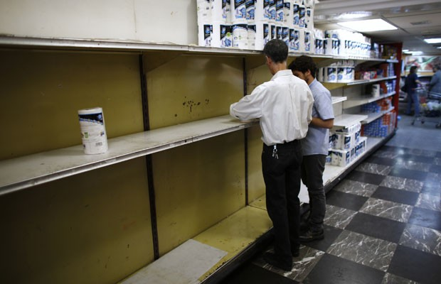 Funcionários de supermercado trabalham perto de prateleiras vazias de papel higiênico em Caracas, em maio (Foto: Jorge Silva/Reuters)