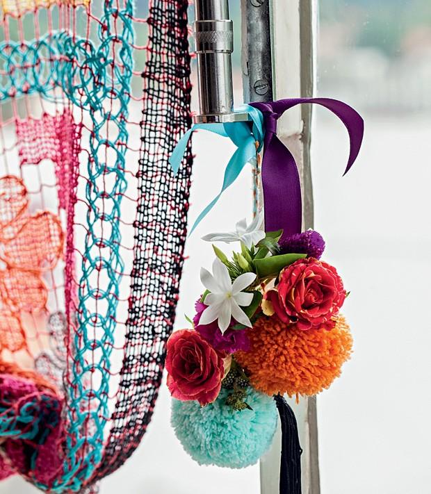 Janela também é espaço para decoração. No puxador, o que acha de amarrar pompons e flores artificiais com uma fita? Escolha cores alegres (como as da foto) para dar vida ao ambiente. (Foto: Elisa Correa/Casa e Comida)