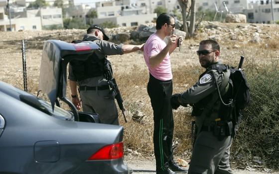 A polícia de fronteira israelense revista um palestino, em um dos acessos a Jerusalém Oriental  (Foto: AP Photo/Mahmoud Illean)