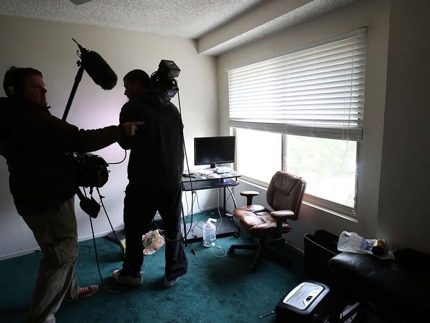 Repórteres são vistos dentro da casa dos suspeitos no tiroteio de San Bernardino, Syed Farook e Tashfeen Malik, durante visita da imprensa na sexta (4) (Foto: Justin Sullivan/Getty Images/AFP)