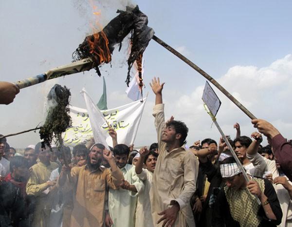 Afegãos queimam figura de Barack Obama em protesto em Khost, sudeste de Cabul. Alguns universitários protestaram contra o filme considerado ofensivo ao Islã. (Foto: Nashanuddin Khan/AP)