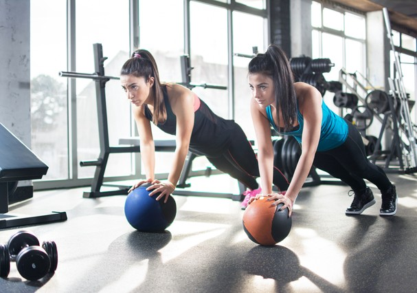 Young women doing stretching exercises on fitness ball in gym. (Foto: Getty Images/iStockphoto)