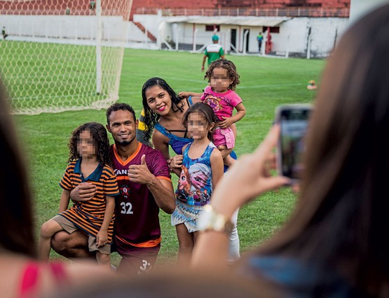 Bruno posa para fotos com crianças.Ele age como idolo apesar de poder voltar para cadeia (Foto: Adriano Vizoni/Folhapress)
