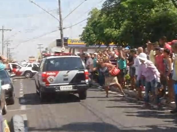 Moradores tentam bater na viatura que levava o suspeito preso (Foto: Reprodução / TV TEM)