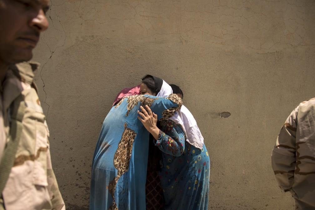 Mulheres se abraçam enquanto aguardam autorização para voltarem para suas casas, localizadas em um dos últimos redutos do Estado Islâmico em Mossul (Foto: Fadel SENNA / AFP)