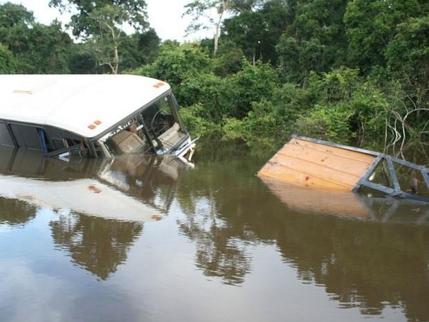 Ônibus que tentou atravessar estrada inundada ficou preso na água, e trator que tentou rebocá-lo também (Foto: Ivanir Valentim/TV Amazonas)