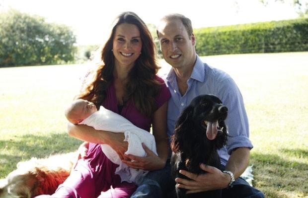 Imagem datada do começo de agosto mostra o príncipe William, a duqesa de Cambridge e o bebê George. Aparecem também na foto os cães Tilly (golden, à esquerda) e Lupo. A foto foi tirada pelo pai de Kate, no jardim da residência oficial da família Middleton (Foto: AFP)
