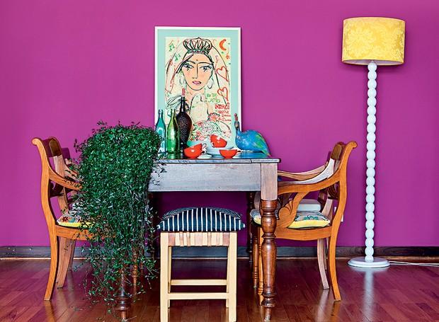 O quadro de Isabelle Tuchband fica apoiado sobre a mesa de jantar da designer Audrey Ammar. A obra contrasta com a parede fúcsia (Foto: Edu Castello e Lufe Gomes/Casa e Jardim)