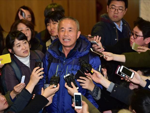 Membro do escritório que representa os interesses do ex-funcionários da Samsung que morreram de câncer, em decorrência de suas atividades, fala com a imprensa depois do acordo alcançado com a companhia (Foto: AFP)