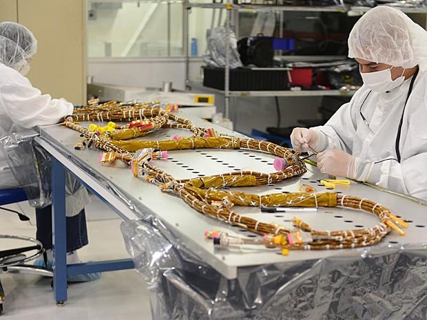 Cabos destinados ao novo satélite são manipulados por funcionários do JPL (Foto: Frederic J. Brown/AFP)