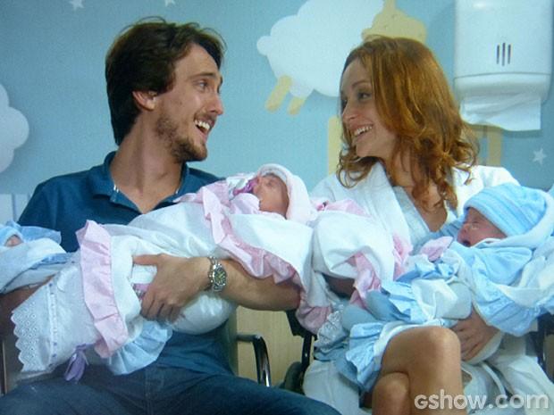 Marcelo e Pri com o riso solto ao segurar os filhos no colo (Foto: Além do Horizonte / TV Globo)