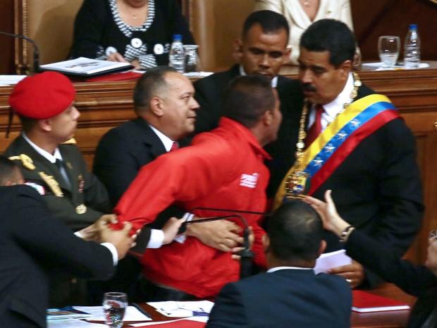 O presidente da Assembleia Nacional, Diosdado Cabello, e seguranças seguram um homem de jaqueta vermelha que tenta se aproximar de Nicolás Maduro durante a cerimônia de posse (Foto: Francisco Boza/AFP)