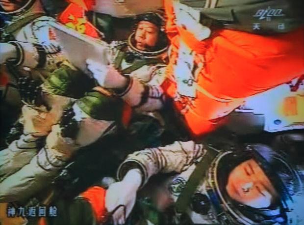 Os astronautas chineses Liu Wang, Jing Haipeng e Liu Yang aparecem no telão gigante do centro espacial Jiuquan. Navegando a Shenzhou-9, eles se acoplaram ao módulo Tiangong-1 (Foto: AFP)