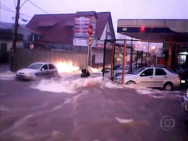 Homem se segura em poste durante chuva forte em BH (Foto: Reprodução/TV Globo)