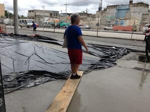 Idosa tenta passar em ponte improvisada por causa de obra na calçada (Foto: Káthia Mello/G1)