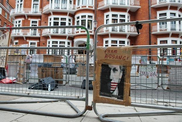 """Foto do fundador do WikiLeaks com a inscrição """"Liberdade para Assange"""" é colocado em grade de proteção de embaixada equatoriana em Londres, onde ele aguarda resposta a pedido de asilo (Foto: Will Oliver / AFP)"""