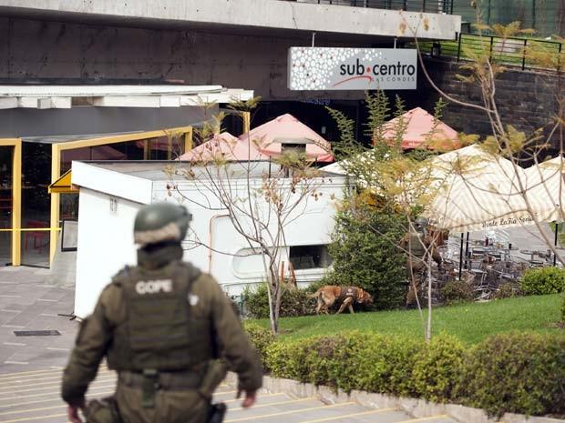 Policial chileno e cachorro da polícia inspecionam estação Escuela Militar do metrô de Santiago, onde houve uma explosão nesta segunda-feira (8) (Foto: AFP PHOTO/VLADIMIR RODAS)