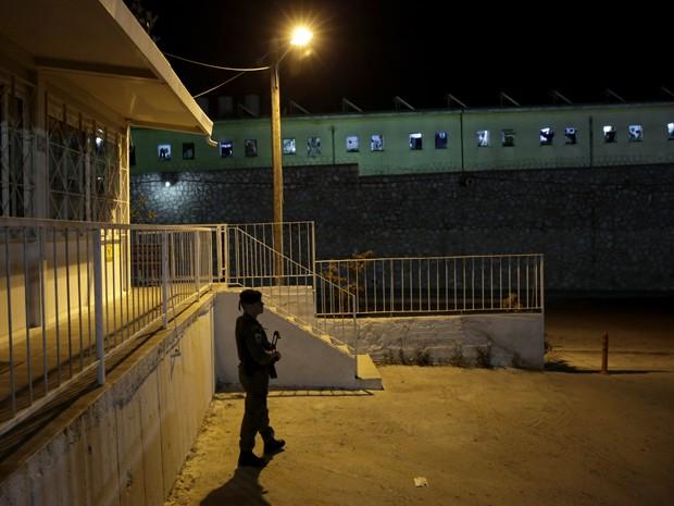 Policial patrulha área externa da prisão Korydallos, em Atenas, no domingo (3), após briga entre detentos que deixou dois mortos (Foto: AP Photo/Petros Giannakouris)