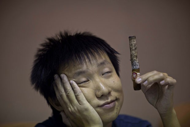 Participante relaxa após fumar charuto (Foto: Ramon Espinosa/AP)