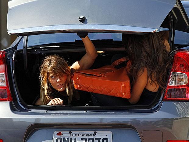 Jéssica e Morena pulam dentro do bagageiro de um carro (Foto: Salve Jorge/TV Globo)