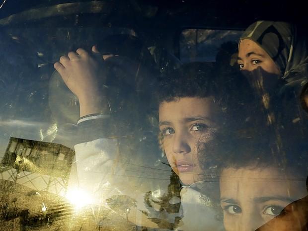 Crianças refugiadas sírias olham através da janela do carro enquanto cruzam a fronteira do Líbano com suas famílias em Masnaa, no leste do Líbano. (Foto: Hassan Ammar/AP)
