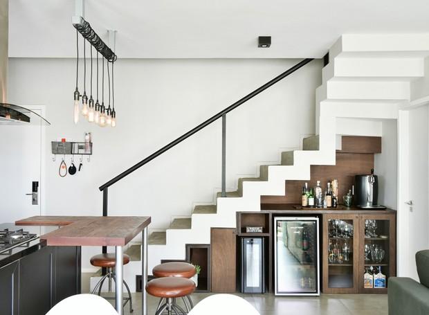 BAR | A escada em cimento queimado foi preservada do projeto original. O espaço abaixo foi aproveitado para abrigar o bar. O móvel em MDF madeirado foi desenhado pela arquiteta Thaysa Camargo com iluminação embutida (Foto: Sidney Doll/Divulgação)