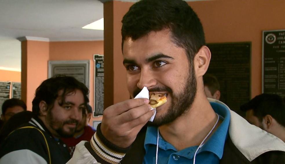Sandro Ferreira aproveita para provar mini pizza com insetos em café na Unesp em Jaboticabal, SP (Foto: Antônio Luiz/EPTV)