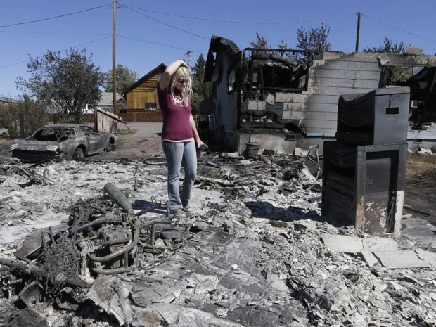 Mulher observa o que sobrou da casa dela após ser atingida por incêndio em Weed, na Califórnia (Foto: Rich Pedroncelli/AP)
