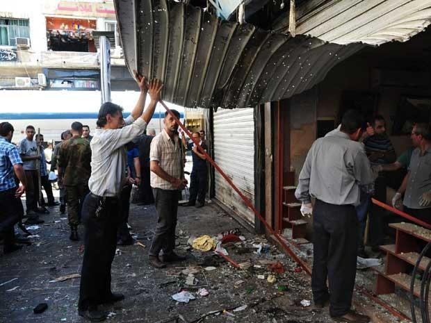 Sírios inspecionam loja danificada após duas explosões no Centro de Damasco. (Foto: Agência estatal Sana /AP Photo)