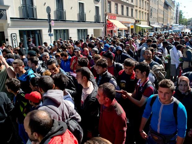 Refugiados são encaminhados a abrigo em Munique neste sábado (12) (Foto: Sven Hoppe/AP)