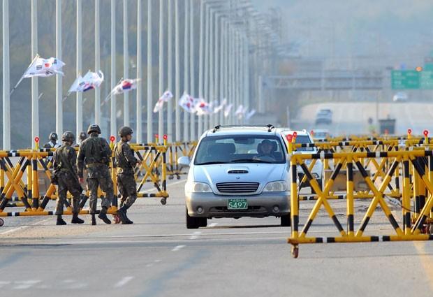 Soldados da Coreia do Sul vigiam barricadas montada no caminho para o complexo industrial de Kaesong nesta sexta-feira (26). A Coreia do Sul vai retirar todos os seus trabalhadores remanescentes das fábricas (Foto: Jung Yeon-Je/AFP)