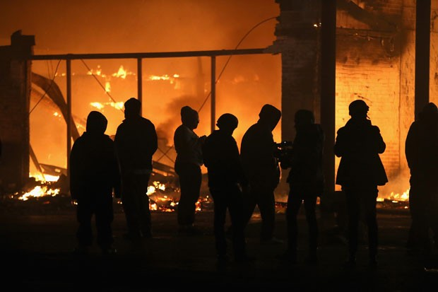 Manifestantes olham prédio pegar fogo durante protesto na madrugada desta terça-feira (25) em Ferguson (Foto: Wilson. Scott Olson/Getty Images/AFP)