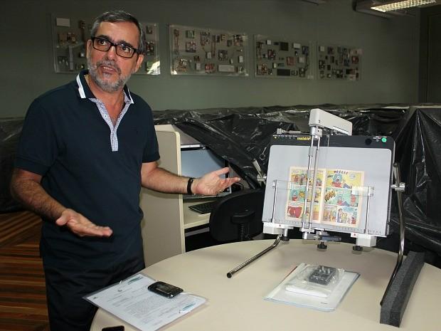 Secretário exibe uma das novidades da biblioteca: folheador automático (Foto: Adneison Severiano/G1 AM)