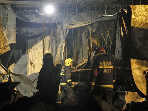 Bombeiros vasculham escombros de abatedouro de aves em busca de sobreviventes. Incêndio matou mais de 100 pessoas na China. (Foto: STR / AFP)