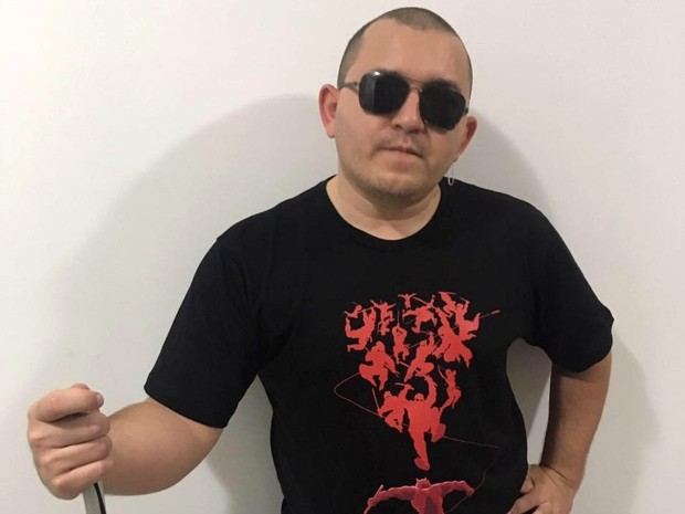 Sidney está enconstado numa parede branca, de óculos escuros, vestido com uma camisa preta com a estampa vermelha de alguns ninjas e segurando uma bengala (Foto: Sidney Andrade/Arquivo Pessoal)