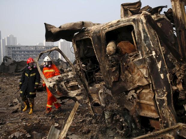 Bombeiros caminham próximo a um caminhão danificado no local das explosões de quarta-feira em Tianjin, na China (Foto: REUTERS/China Daily)