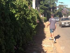 Eurípedes têm que desviar de buracos na calçada e carros para caminhar próximo ao Jardim Botânico, em Goiânia (Foto: Paula Resende/ G1)