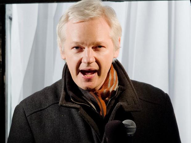 Julian Assange discursa de dentro da embaixada equatoriana em foto tirada em dezembro (Foto: Leon Neal/AFP)