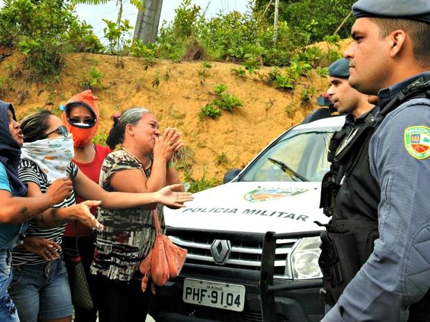 Familiares de presos cobrem rostos e pedem informações de policiais do lado de fora do Compaj, em Manaus (Foto: Isis Capistrano / G1 AM)
