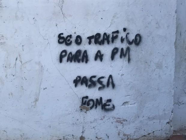 """Pichação no muro do cemitério onde foi encontrado drogas e armas com a frase """"se o tráfico para, a PM passa fome"""" (Foto: Walter Paparazzo/G1)"""