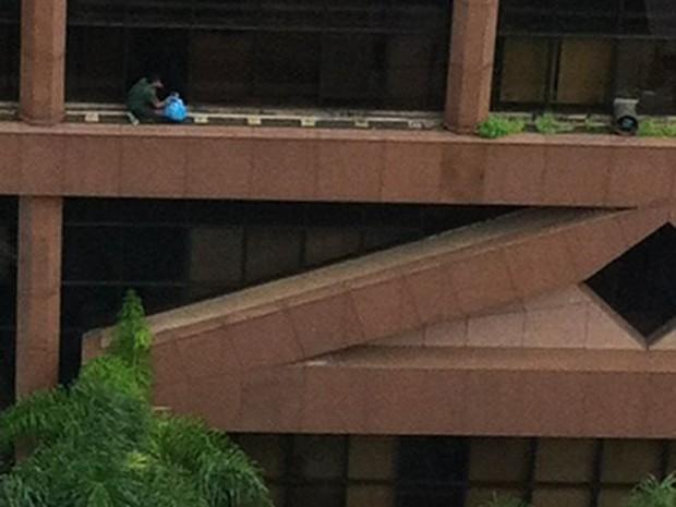 Funcionário limpa fachada de tribunal trabalhista sem equipamento de segurança, em Campinas (Foto: Reprodução / EPTV)