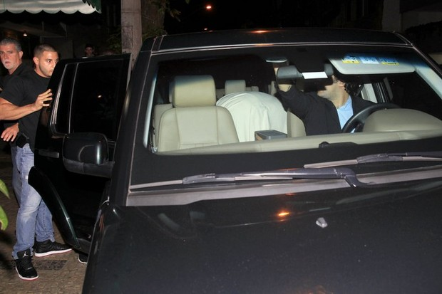 Justin Bieber entra no carro enrolado no lençol (Foto: Francisco Silva/Agnews)