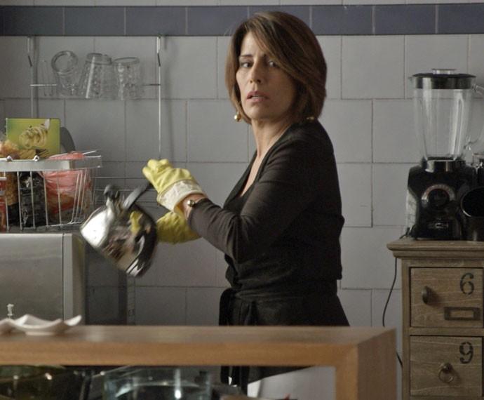 Beatriz liga o gás do fogão e fecha as janelas (Foto: TV Globo)