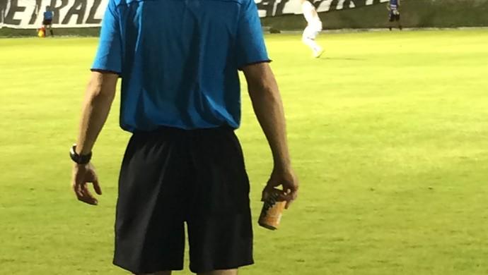 Quarto árbitro recolhe lata arremessada por torcedor do América-RN (Foto: Alexandre Filho/GloboEsporte.com)