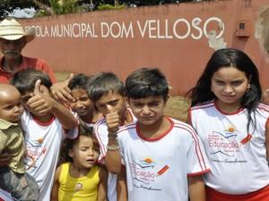 Idoso posa ao lado dos netos que estudam na Escola Dom Velloso, em Itumbiara, Goiás (Foto: Adriano Zago/G1)